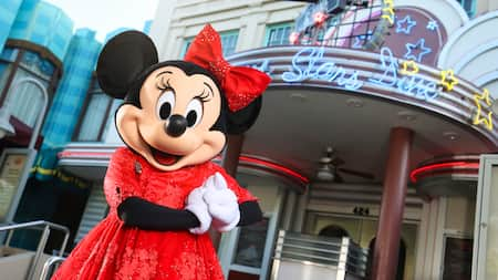 Minnie Mouse stands in holiday attire in front of Hollywood and Vine restaurant in Disney's Hollywood Studios