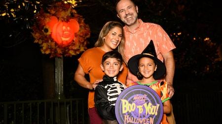 Perto de uma abóbora do Mickey iluminada em um poste de luz, um menino e uma menina fantasiados fazem uma pose com os pais atrás de uma placa onde se lê Mickeys Boo to You Halloween Parade