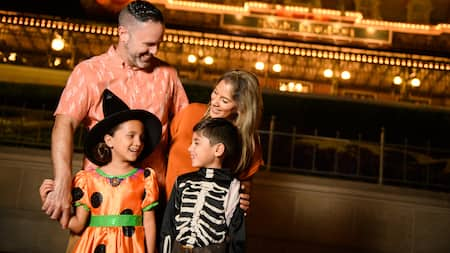 A young boy and girl dressed in Halloween costumes stand with their parents outside a Walt Disney World Resort hotel at night