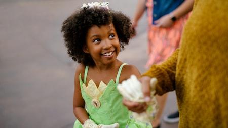 Une petite fille habillée en Tiana sourit et tient la main de sa mère