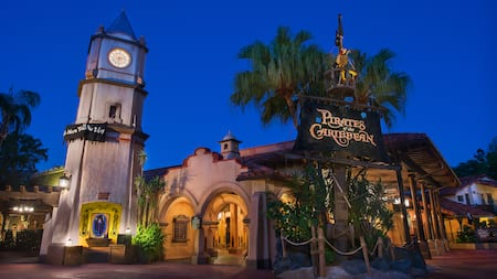 A clock tower and a pirate skeleton in a crows nest next to the Pirates of the Caribbean entrance
