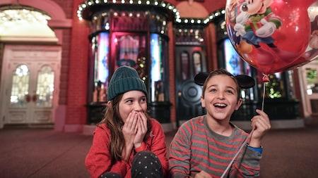 Um menino segurando um balão sentado na Main Street USA com a irmã