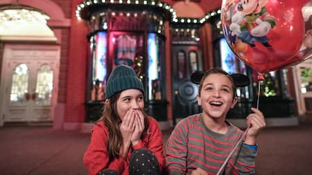 A boy holds a balloon while sitting on Main Street USA with his sister