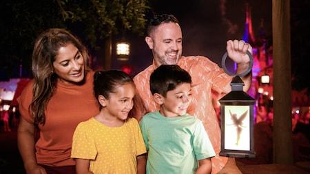 Une famille de quatre à Fantasyland sourit en voyant Fée Clochette à l'intérieur d'une lanterne