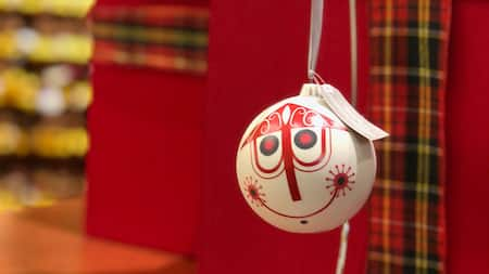 A Christmas ornament, decorated in the quirky style of Disney artist Mary Blair, hangs from a ribbon