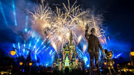 A fireworks and light display at Cinderella Castle behind the Walt Disney and Mickey Mouse statues