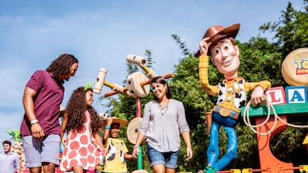 A family holds hands in Toy Story land while passing oversized toys and a oversized statue of Woody