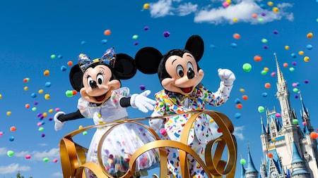 Mickey y Minnie en una carroza frente a Cinderella Castle mientras confeti vuela en el aire