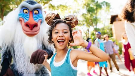 A girl in a Minnie Mouse headband holds hands with Rafiki at Disney's Animal Kingdom Theme Park