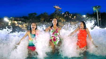 3 teen Guests stand side by side, thrilled by a splashy wave