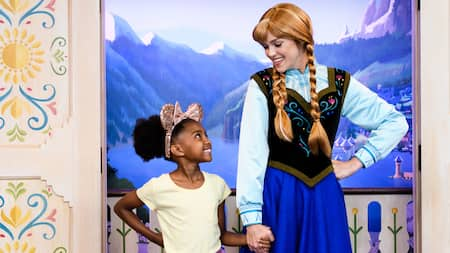 A young girl holding hands with Anna from Frozen in front of a backdrop depicting the land of Arendelle
