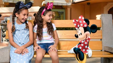 Two little girls wearing mouse ears sit on a wooden bench next to an animated image of Minnie Mouse