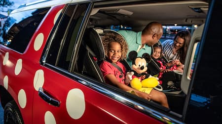 Parents secure their 2 little girls in car seats aboard a Minnie Van service vehicle