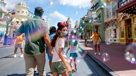 A family walking down Main Street USA at Magic Kingdom park, while Cast Members wave at them