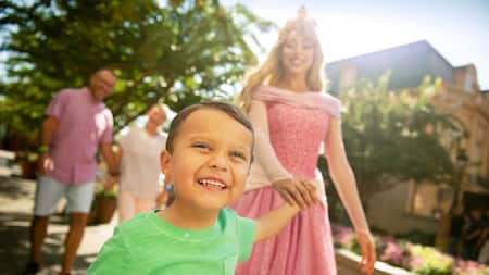 A young boy holds the hand of Princess Aurora as his parents look on from behind