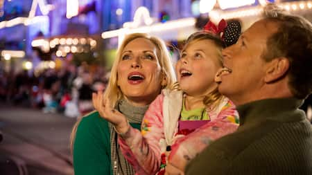 A mother and father hold up their daughter as they delight at decorations at Magic Kingdom park