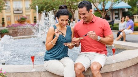 Um homem e uma mulher sentados na beirada de um chafariz com taças de champanhe e comida