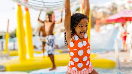 A little girl hangs from monkey bars in a water play area as other children play around her
