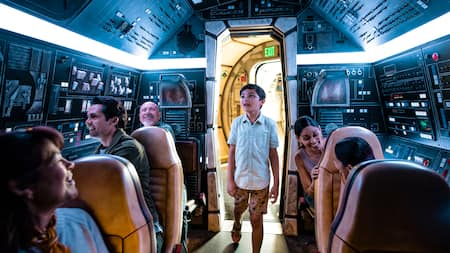 A boy appears fascinated as he looks around the cockpit of the Millennium Falcon