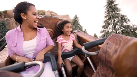 A woman and her daughter smiling while riding on the Seven Dwarfs Mine Train coaster