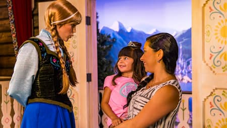 Anna from 'Frozen' smiling while greeting a young girl and her mother