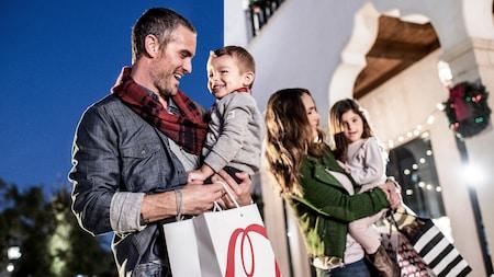 Una madre y un padre cargan a sus 2hijos mientras caminan al aire libre por Disney Springs