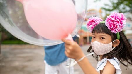 Una niña sostiene el globo de Mickey y corre con su padre