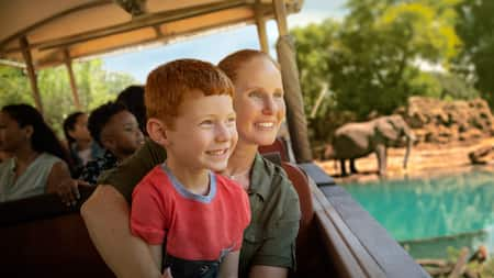 A mom, her son and other passengers sit in a jeep while passing elephants during the Kilimanjaro safari