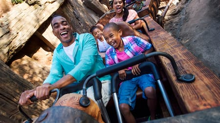 A family of four laughs together while riding Seven Dwarfs Mine Train