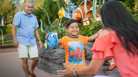 Near The Seas with Nemo & Friends, a small boy with a Dory doll runs to his mom as his dad follows
