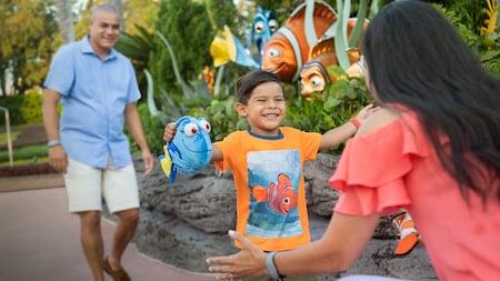 Cerca de The Seas with Nemo & Friends, un niño pequeño con un juguete de Dory corre hacia su madre mientras su padre lo sigue
