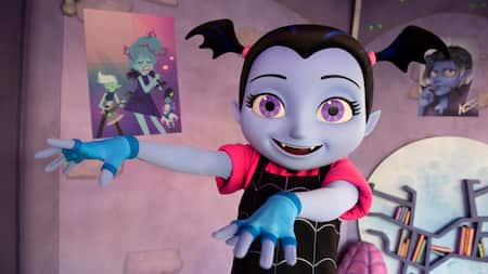 A happy Vampirina stands with outstretched arms in her poster filled room