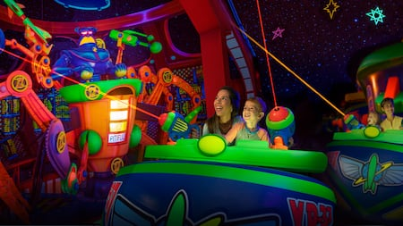 A mother and her child shoot blasters at various targets on Buzz Lightyear's Space Ranger Spin
