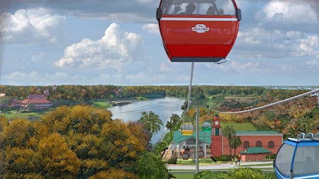 Two people wave from inside a Disney Skyliner gondola travelling over trees near a body of water