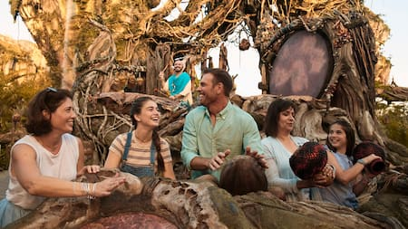 A family of 5 participating in a drum circle amid the exotic plants and floating mountains of Pandora The World of Avatar