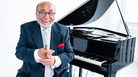 Musician Eddie Palmieri holding a cigar and sitting next to a piano
