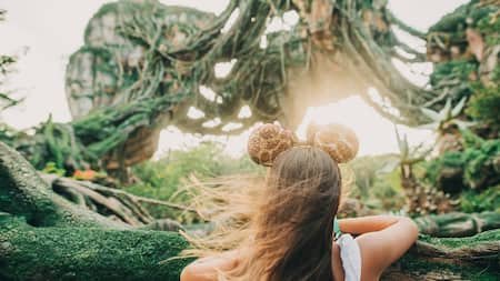 Young girl looks into Pandora World of Avatar floating mountains in her giraffe printed Mickey ears