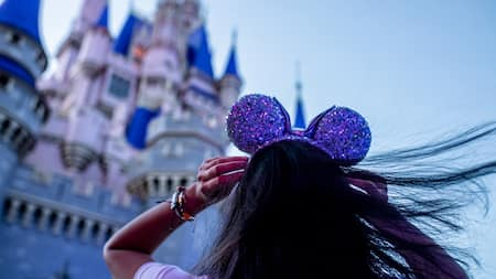 Girl stands in front of Cinderella's Castle at Disney World with purple mickey ears on