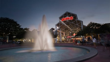 A decorative fountain in front of the AMC Disney Springs 24 theater at dusk