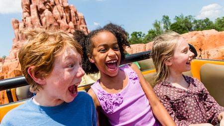 Três crianças gritam felizes enquanto passeiam na Big Thunder Mountain Railroad no Magic Kingdom Park