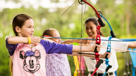 Young Guests take aim with bows and arrows while an instructor looks on