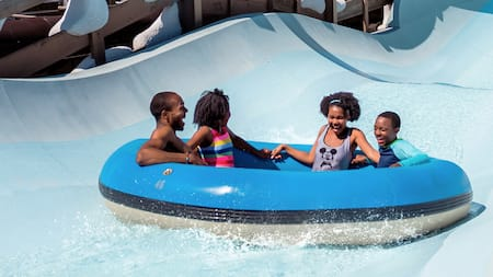 A family of 4 rides a raft down a large waterslide that is themed to look like it is covered in snow