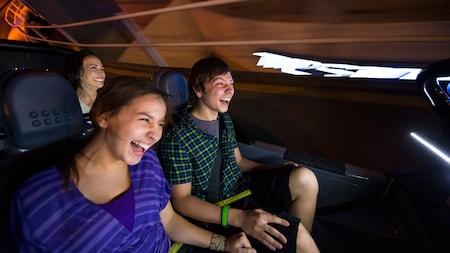 Três visitantes sorriem ao darem uma volta em um carro SIM na Test Track apresentada por Chevrolet