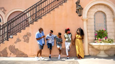 Family stands in World Showcase against a wall enjoying food