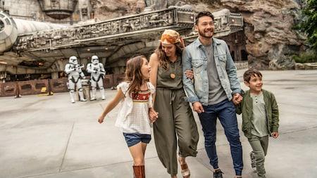 Una familia en Star Wars:Galaxy's Edge cerca de Stormtroopers de la Primera Orden y, al fondo, el Millennium Falcon