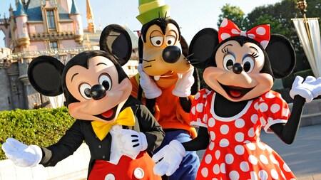 Mickey Mouse, Goofy y Minnie Mouse posan frente al Castillo de la Bella Durmiente