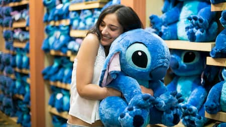 A happy Guest embraces a Stitch plush toy in a store