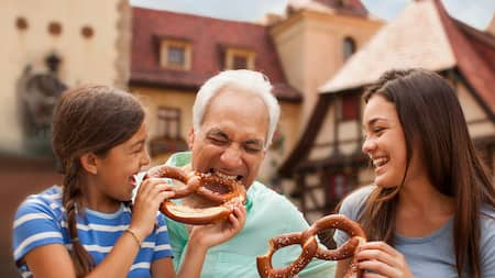 Grandfather bites playfully into a huge pretzel his granddaughter offers, while big sister laughs