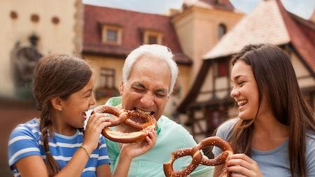 Un grand-père prend une bouchée d'un gros bretzel que lui tend sa petite fille alors que sa grande sœur rit
