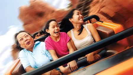 A mother and her daughters smiling excitedly while enjoying a ride on Big Thunder Mountain Railroad